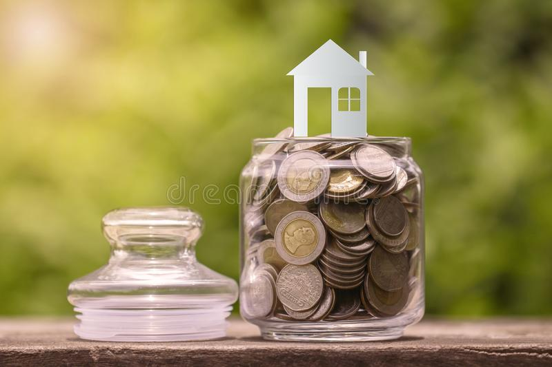House model on coins in glass jar, saving to buy house. House model on coins in glass jar, saving to buy a house royalty free stock images