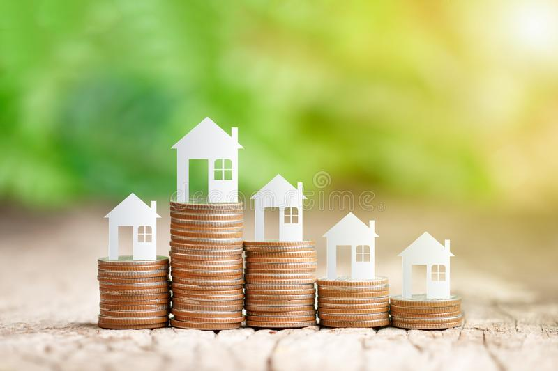 House model on coins stack for saving to buy a house. Paper house model on coins stack for saving to buy a house stock photography