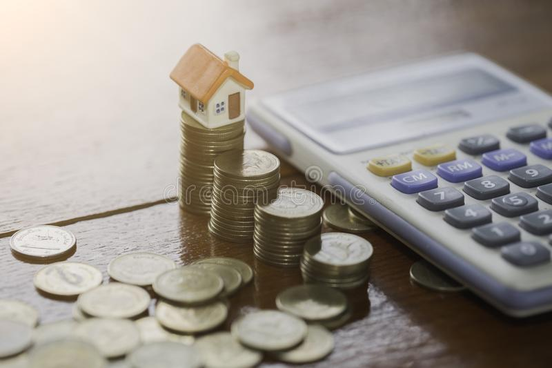 House model on coins stacks with calculator as background. Concept for property ladder, mortgage and real estate investment. royalty free stock photo