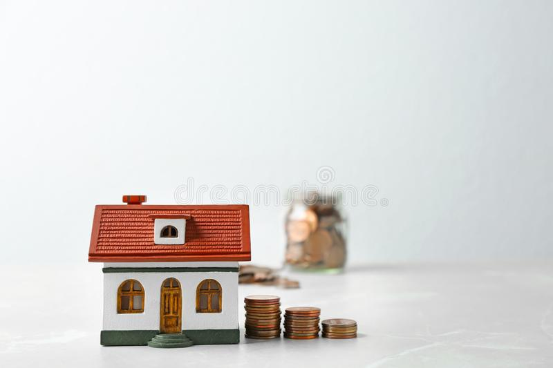 House model and coins on table against light background. Space for text stock photo