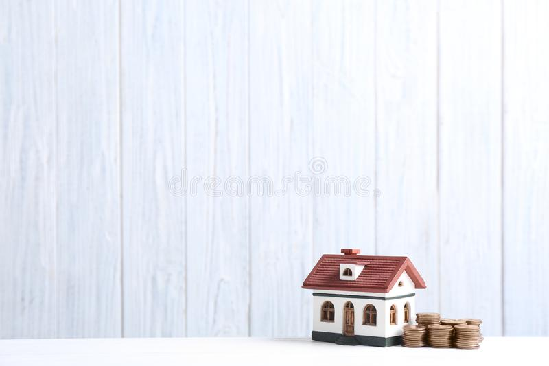 House model and coins on table against wooden background. Space for text stock photography