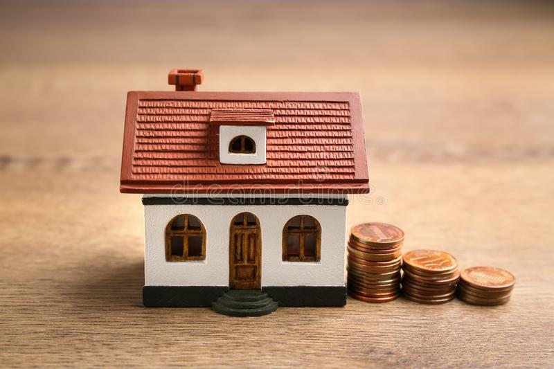 House model and coins. Money saving concept stock image