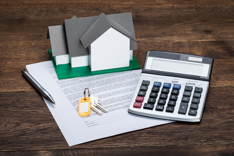 House Model On Contract Paper With Keys And Calculator. Kept On Wooden Desk stock photography