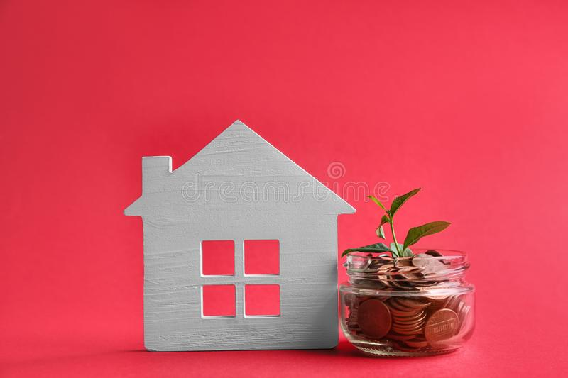 House model, jar with coins and plant on color background. Space for text royalty free stock image