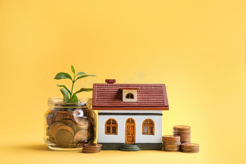 House model, jar with coins and plant on color background. Space for text royalty free stock photos