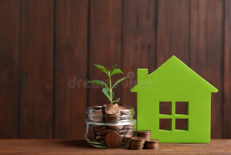 House model, jar with coins and plant on table against wooden background. Space for text royalty free stock photos