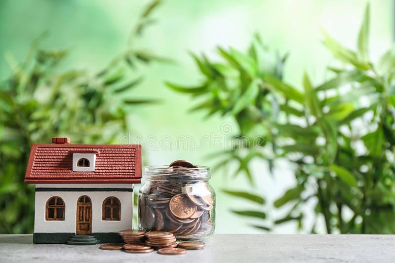 House model and jar with coins on table against blurred background. Space for text royalty free stock photo