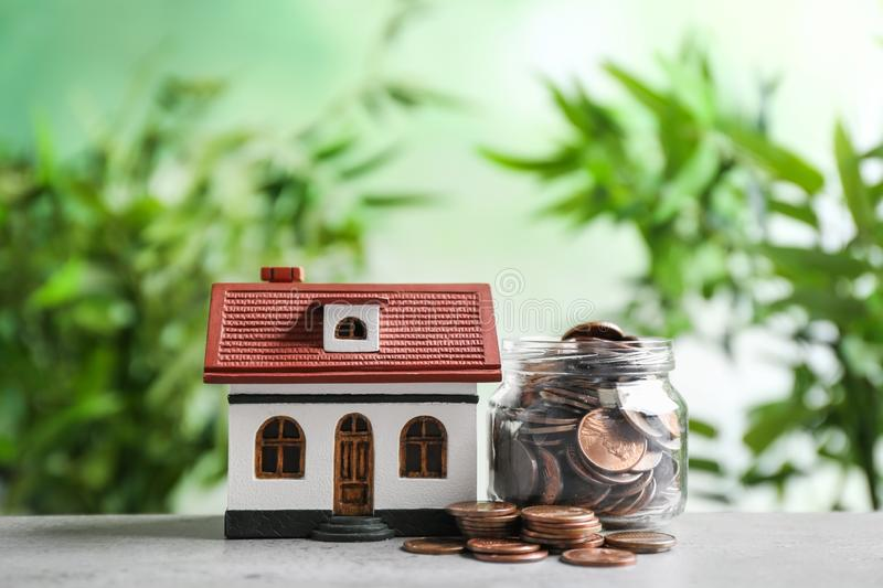 House model and jar with coins on table against blurred background. Space for text stock photo