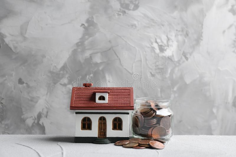 House model and jar with coins on table against grey background. Space for text royalty free stock image