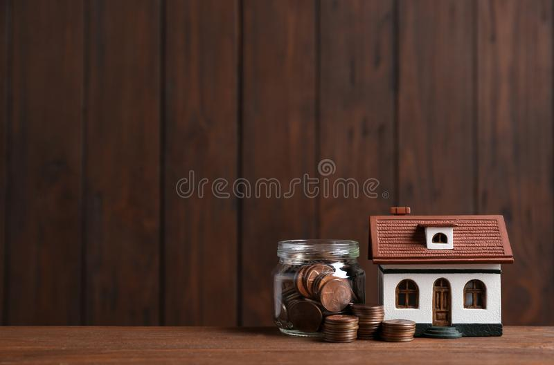 House model and jar with coins on table against wooden background. Space for text stock image