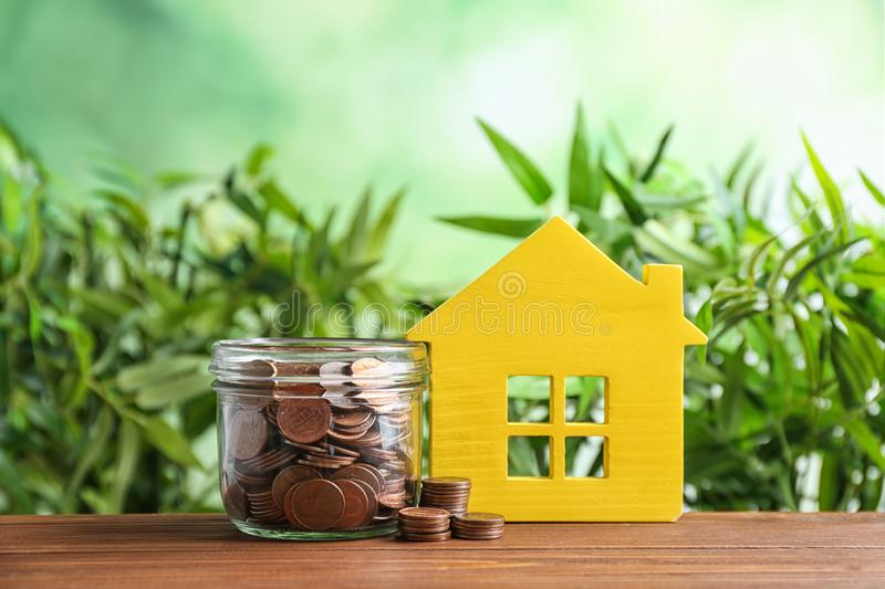 House model and jar with coins on wooden table against blurred background. Space for text stock images