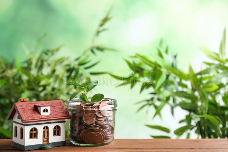 House model and jar with coins on wooden table against blurred background. Space for text royalty free stock photo