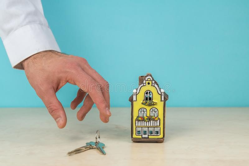 House model and key in hand, real estate concept, turquoise color copy space. Nice house model and key in hand, turquoise background for copy space - real royalty free stock photos