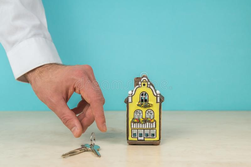 House model, key and hand, real estate concept, turquoise color copy space. Nice house model, key and hand, turquoise background for copy space - real estate royalty free stock image