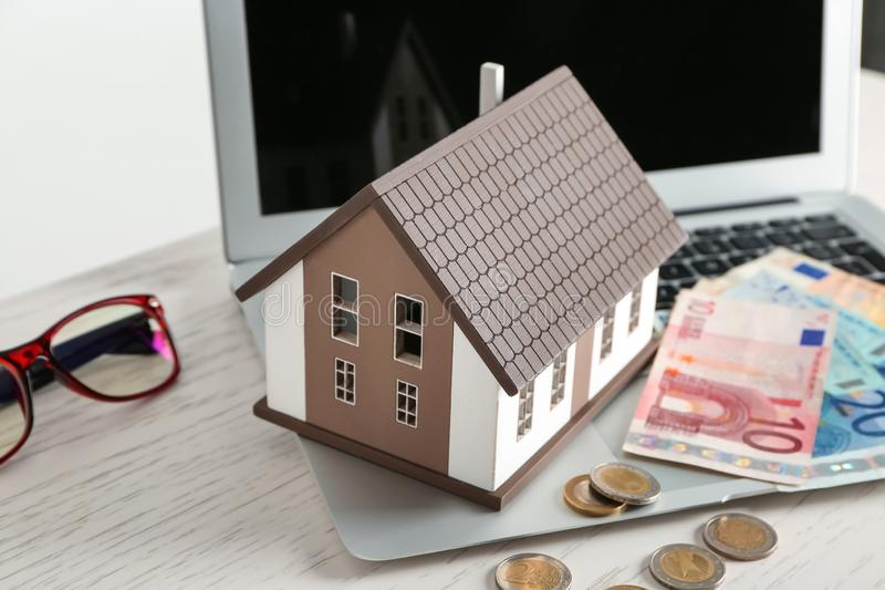 House model, laptop and money on table. Mortgage concept stock images