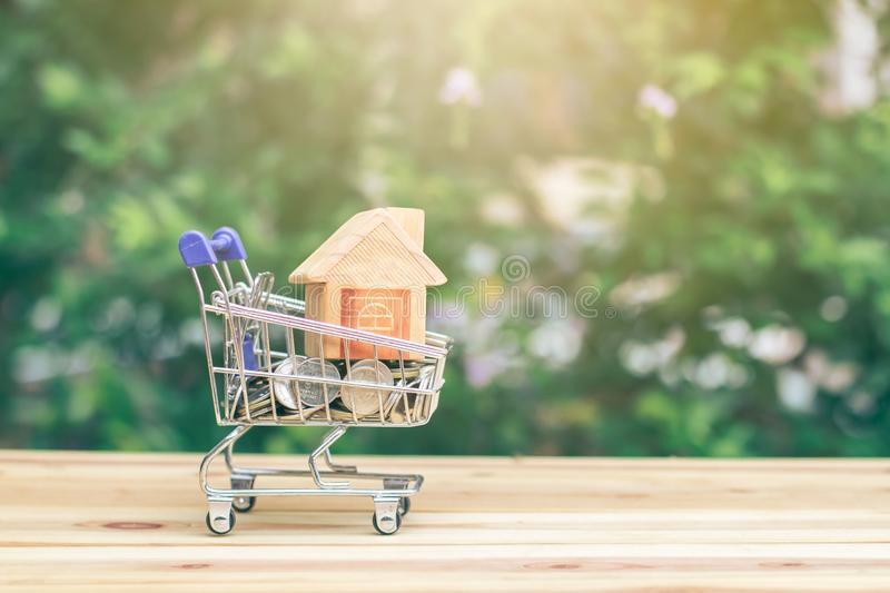 House model in mini shopping cart with stack of coins money in the Cart for residential investment. stock image
