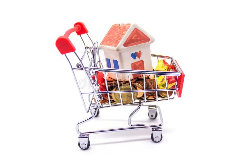 House model in mini shopping cart with stack of coins money on white blackground.  stock photo