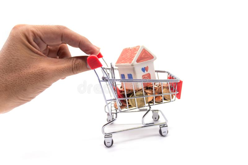 House model in mini shopping cart with stack of coins money on white blackground.  stock photography