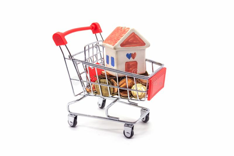 House model in mini shopping cart with stack of coins money on white blackground.  stock images