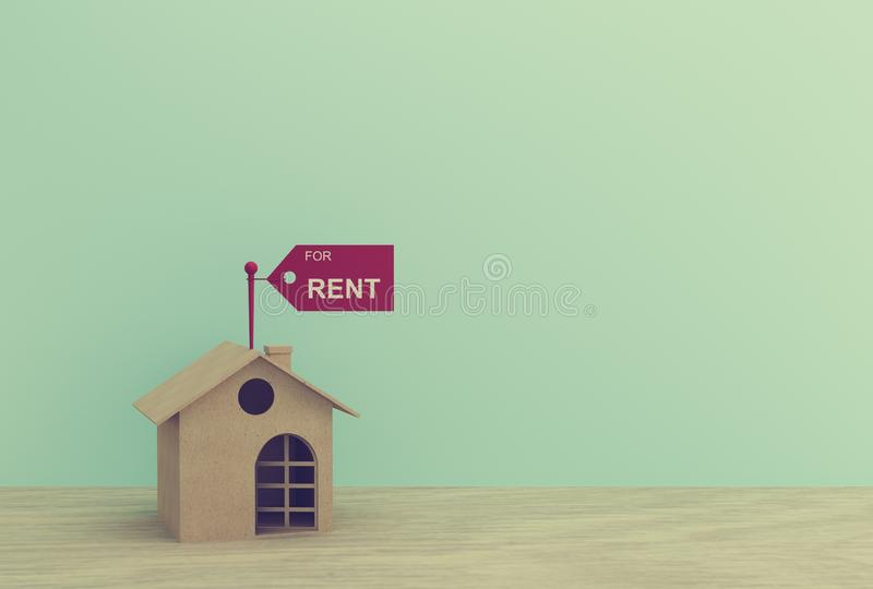 House model with a paper tag and chain on wood table with blue background. depicts a payment for temporary use of a property owned. By another owner, tenant royalty free stock photography