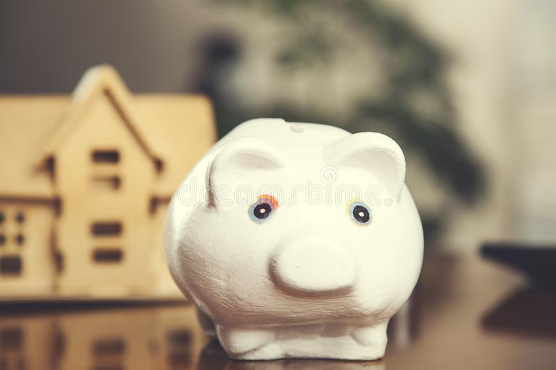 House model with piggy bank. On desk royalty free stock image