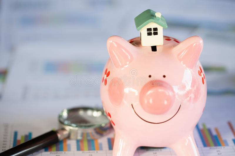 A house model placed on a piggy bank, finance and banking, Saving money and property Management concept.  stock photos