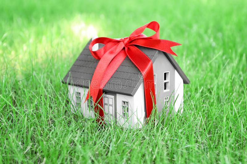 House model with ribbon on green lawn. Mortgage concept royalty free stock photography