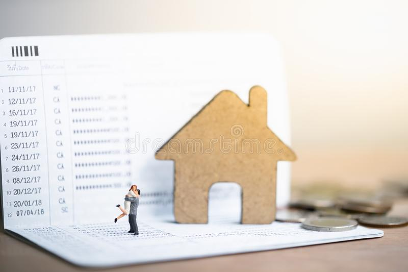 House model and small couple figures in love standing on bank passbook. stock photos