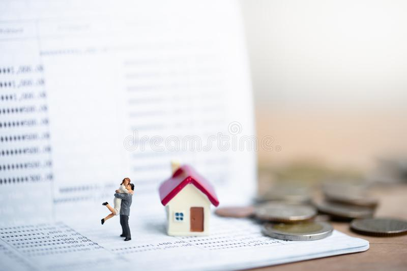 House model and small couple figures in love standing on bank passbook. Love and Valentine`s day concepts. family finance concept. Saving money for get royalty free stock image