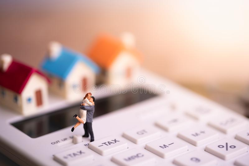 House model and small couple figures in love standing on calculator. royalty free stock images