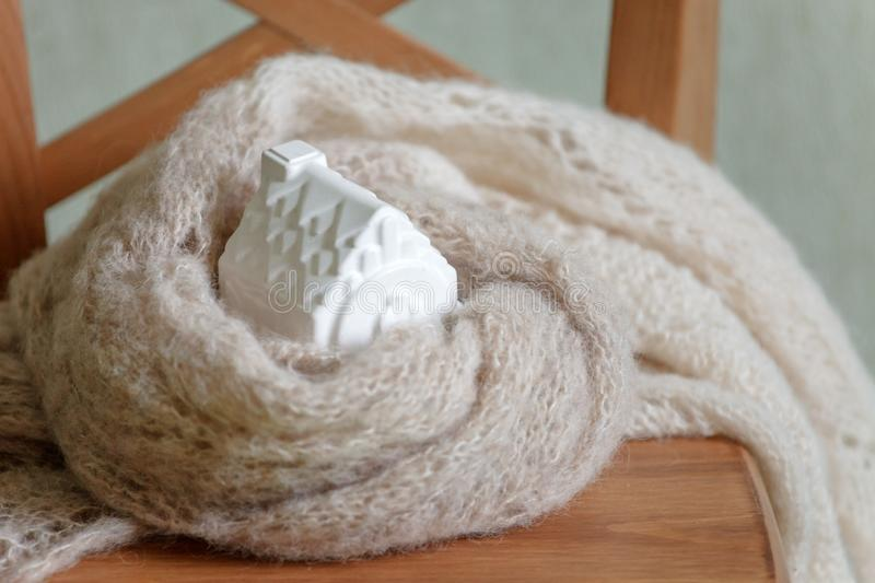 House model toy. Warm house concept, Heating efficiency. environmentally friendly warm home wrapped in a soft comfortable scarf stock image