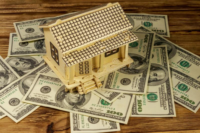 House model and U.S. one hundred dollar bills on wooden background. Property investment, home loan, house mortgage, real estate stock images
