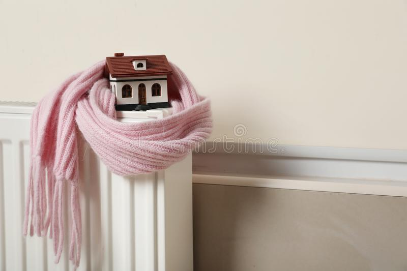 House model wrapped in pink scarf on radiator, space for text. Heating efficiency. House model wrapped in pink scarf on radiator indoors, space for text. Heating stock image