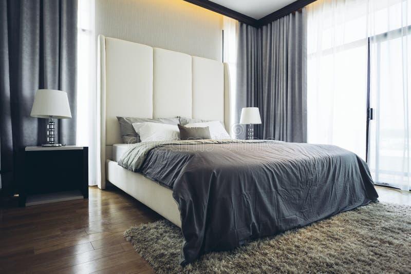 House modelo moderno italiano: Dormitorio gris y blanco del esquema de color fotos de archivo