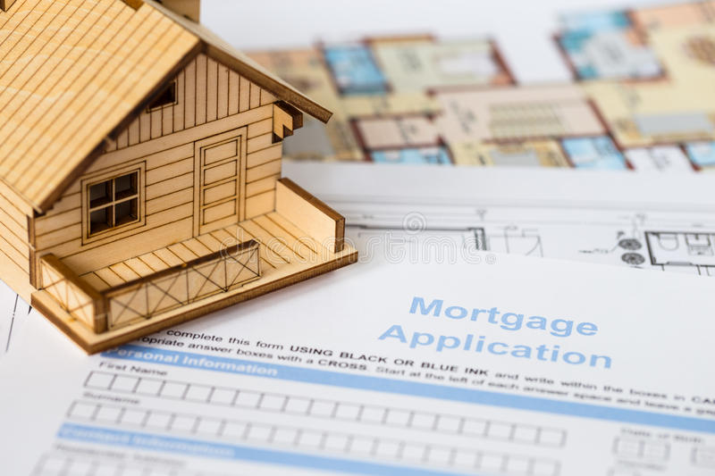 House mortgage application with model house. And construction plan stock photos