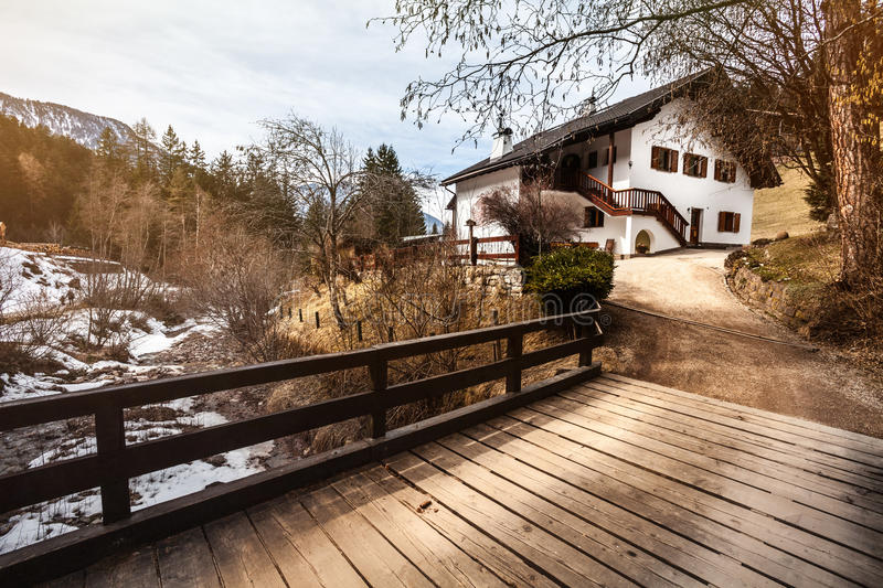 House in the mountains, snow and wooden bridge. Mountain home. A rustic mountain home. A bridge with wooden planks, river with snow, mountains and forest stock photography