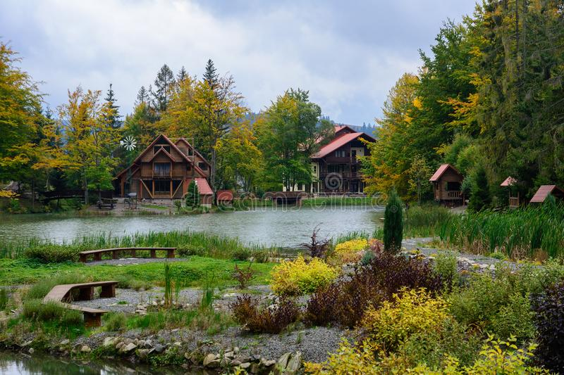House near the lake in the forest, autumn day. stock photo