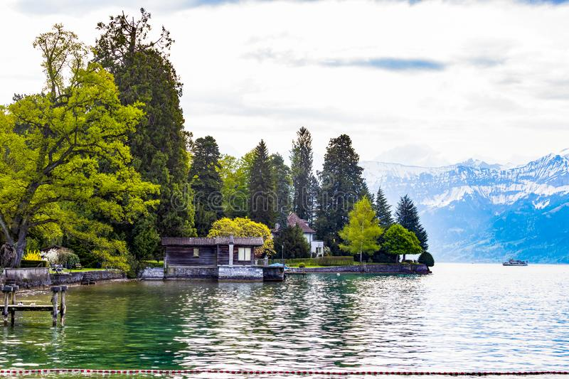 House near lake Thun and travek ship with view of Bernese Alps mountain Berne, Switzerland. Europe royalty free stock photo