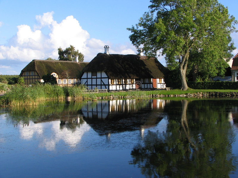 House near the pond in Danmark. Old white house with a tree in in Danmark stock image