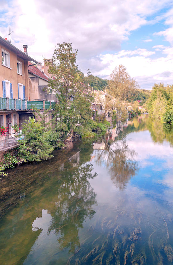 House nears the river. House along the river in France on a sunny day. It´s a vertical picture stock photography