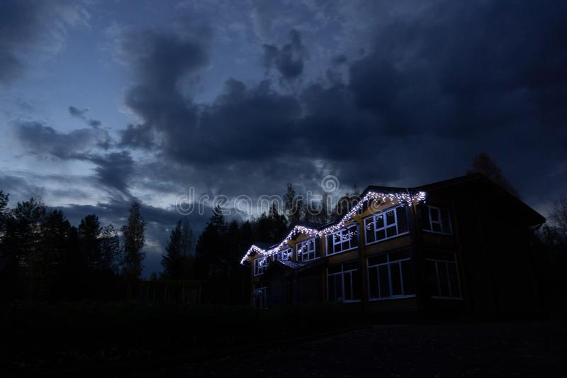 House at night in lights bulbs. Bulbsclouds, color, nature, trees, forest, sky, home royalty free stock images
