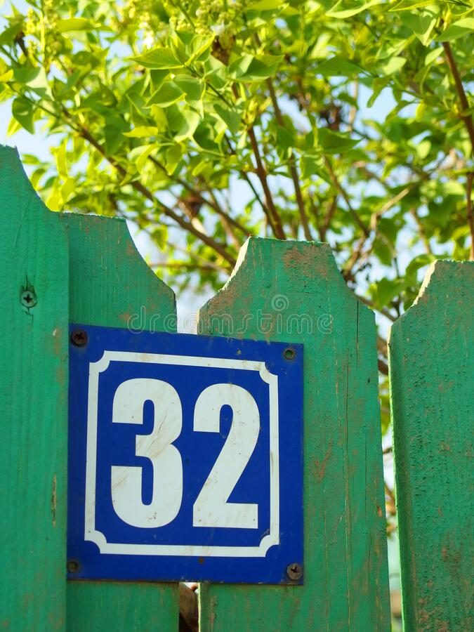 House number 32 on green wooden fence. House number 32 plate, on a green wooden fence, with a green tree in background royalty free stock photo