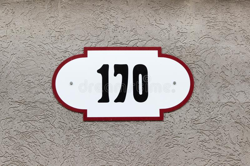 House number 170 one hundred and seventy. Black lettering on a white fashioned metal plate. With brown edge on the wall covered with stucco royalty free stock photo