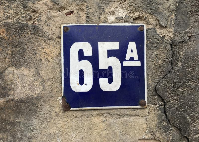 House number plate 65a. Number plate 65a on grunge concrete wall on sunny day stock image