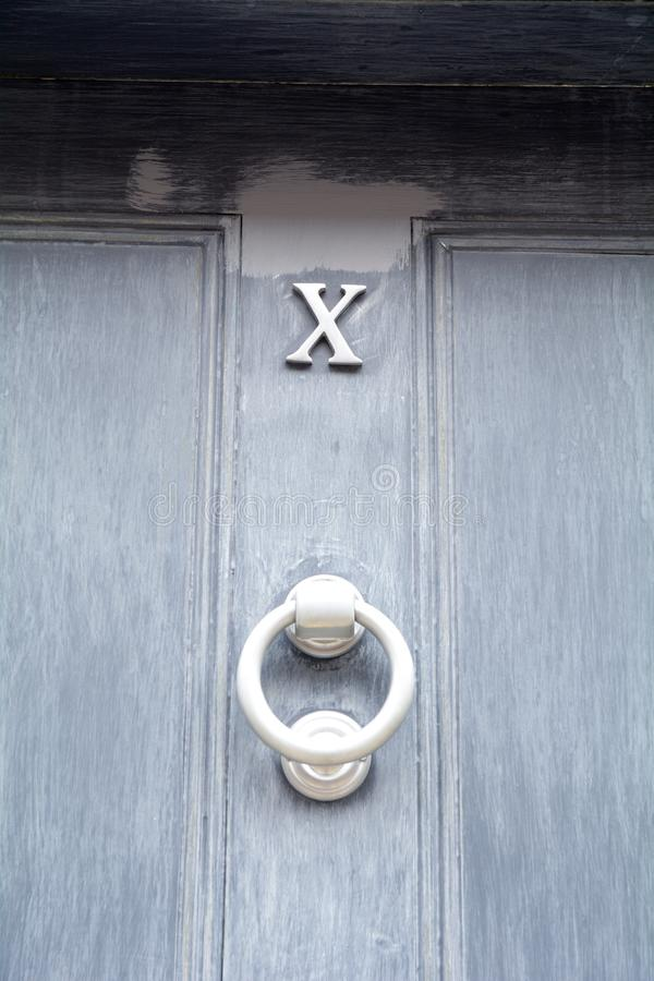 House number 10 shown as Roman numeral X on blue painted door. With knocker royalty free stock image