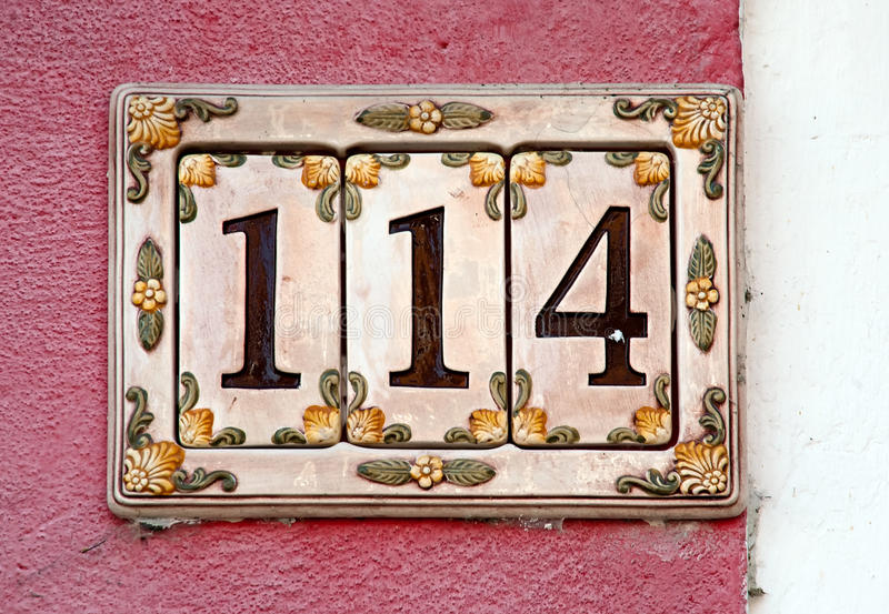 House number sign. Closeup of decorated house number digits sign on the wall royalty free stock photo