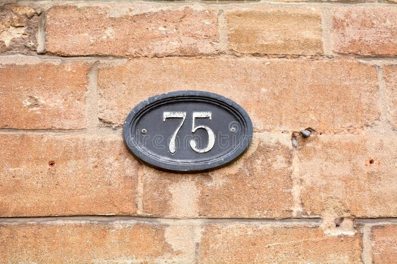 House number 75 sign fixed to brick wall royalty free stock photography