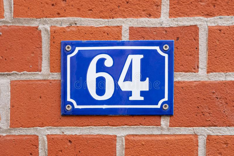 House Number 64. Vintage style house number 64. Metal sign on brick wall royalty free stock photography