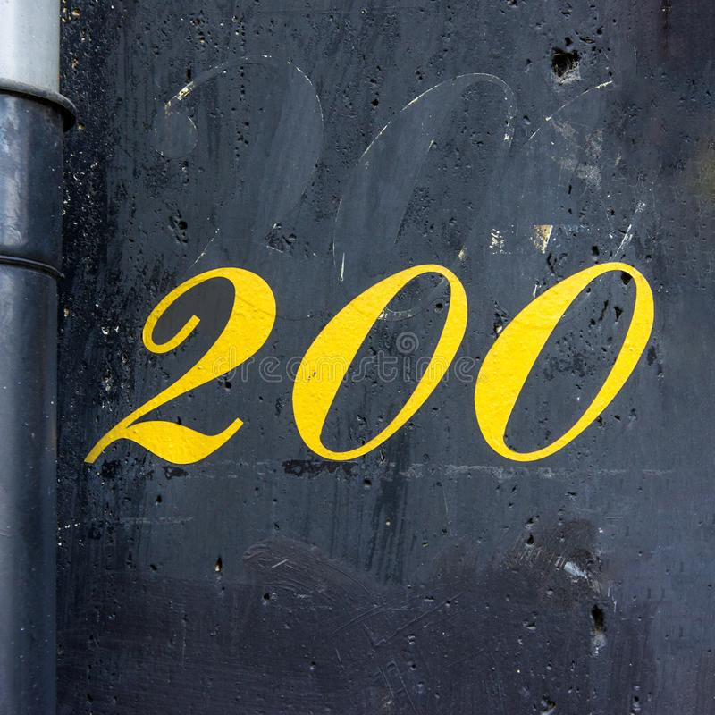 House number 200. Yellow house number two hundred 200 Hand painted on a black wall royalty free stock photography