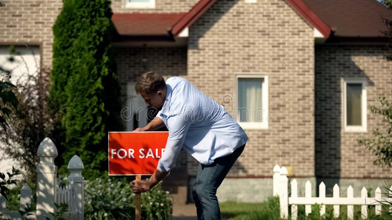House owner installing for sale signboard in front of luxury building, moving. Stock photo stock photo